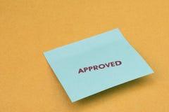 Stempel genehmigt auf blauer Post-Itanmerkung Lizenzfreies Stockbild