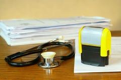 Stempeln Sie und ein Stethoskop auf einer medizinischen Tabelle Stockfoto