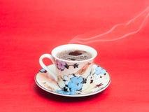 Stemplujący kubek z parującą kawą Miękka część dym Czerwony tło fotografia stock