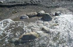 Sten i vattnet som omges av havsskum royaltyfri bild