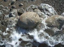 Sten i vattnet som omges av havsskum royaltyfria bilder