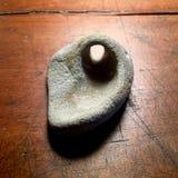 Sten med det naturliga hålet på den antika wood tabellen Royaltyfria Bilder