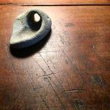 Sten med det naturliga hålet på den antika wood tabellen Arkivbilder