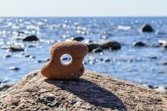 sten med en insida f?r rund form f?r h?l, sikt till och med h?let, mot havet bland stenarna royaltyfri bild