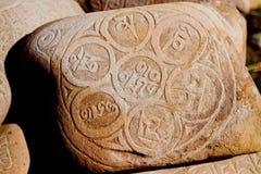 Sten med sanskrit skriftligt i berg Arkivfoto