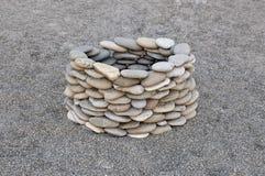 Sten väl på sandstranden Arkivfoto