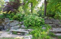 Stena bänken vid grottan och stena moment som omges av vanliga hortensior blommar in, en japansk lönn och annan frodig vegetation Arkivfoton
