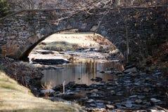 Stena bågen över liten vik med reflexioner i vatten Arkivfoto