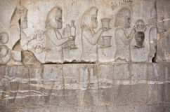 Stena basrelief med hållande mat för forntida folk och kantade vapen i Persepolis, Iran Royaltyfria Foton