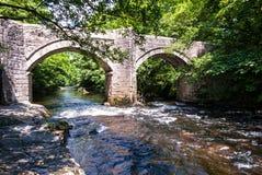 Stena bron över en liten flod, Wales, UK Arkivbilder