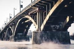 Stena bron på den dimmiga floden royaltyfri foto