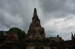 Stena Buddha som framme sitter av en pagod under den molniga himlen Arkivbilder