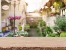 Stena den tomma tabellen för brädet framme av suddig bakgrund Perspektivbruntsten över suddighet i coffee shop royaltyfri fotografi