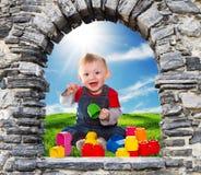 Stena fönster med behandla som ett barn pojken som spelar med mjuka tegelstenar Fotografering för Bildbyråer