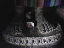 Stena fot som står på sockeln av Buddha, fot med fingrar, mellan benlögnerna en donation, en sedel, en skulptur i ett B Arkivbilder