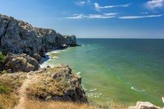 Stena klippor på kusten och den blåa himlen Arkivfoto