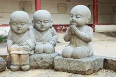 Stena statyn av att lära och koppla av kinesiska munkar Arkivbilder