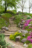Stena trappa i parkera som omges av blommor Arkivfoto
