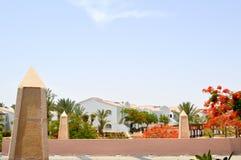 Stena tropiska palmträd för broEgypten bakgrund med gröna och röda sidablommor mot blå himmel för bakgrundsparadislandskapet arkivfoton