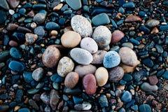 Stenar av olika skuggor och olika ovala former ligger på den steniga kusten av en stor och kall sjö Arkivfoto
