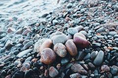 Stenar av olika skuggor och olika ovala former ligger på den steniga kusten av en stor och kall sjö Arkivbild