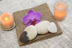 Stenar för massage, stearinljus och en blomma av orkidér på naturliga naturliga servetter, angenäma signaler, en brunnsort Arkivbilder