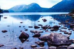 Stenar för natur för vatten för sjön för bergstrandsemesterorten vaggar för trädhimmel för dimma dimmigt lopp för turism för refl Arkivbilder