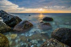 Stenar i förgrunden av havet Arkivbild
