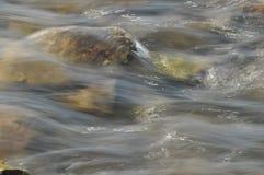 Stenar i floden snabbt flödande vatten Uppfriskande bergflodström Strömmen av crystal vatten Arkivfoton