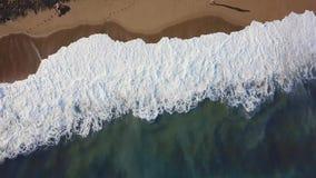 Stenar i hav bevattnar materiel Den bästa sikten av en härlig sandig strand med blåtten vinkar rullning in i kusten sun för hav f stock video