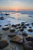 Stenar i havet fryste i isen på solnedgången Royaltyfri Bild
