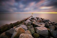 Stenar i havsvatten på bakgrunden av soluppgång Royaltyfri Bild