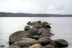 Stenar i lugna vatten, i avståndet en grön kulle Royaltyfria Foton