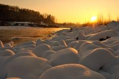 Stenar i snön nära en bergflod i solnedgången tänder Royaltyfria Bilder