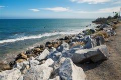 Stenar längs det ojämna kustStilla havet Arkivbild