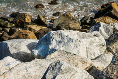 Stenar längs det ojämna kustStilla havet Arkivfoto