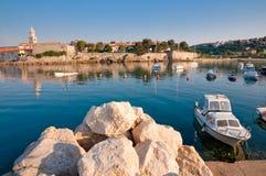 Stenar och fartyg på lite port bredvid den gammala townen Krk - Kroatien Arkivfoton