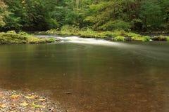 Stenar och forsar i den bidade floden Arkivfoto