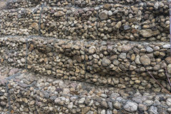 Stenar och metalwire för behållande vägg netto Arkivfoton