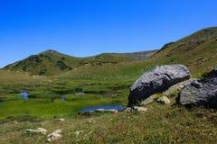 Stenar och små sjöar som omges med alpina ängar i Kaukasus Arkivbild