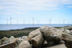 Stenar på strand- och vindturbinbakgrunden Royaltyfria Bilder