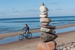 Stenar pyramiden med cyklisten på havet Fotografering för Bildbyråer