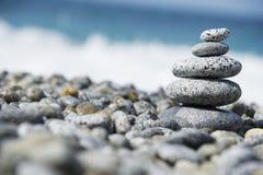 Stenar pyramiden på Pebble Beach som symboliserar brunnsortbegrepp med suddighetshavsbakgrund Arkivfoto