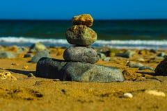 Stenar pyramiden på sand som symboliserar zenen, harmoni, jämvikt Hav i bakgrunden Arkivbild