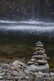 Stenar som staplas med mjukt strömmande vatten i bakgrund royaltyfria foton