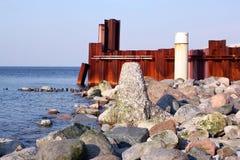 Stenar, vågbrytare och rostig järnvägg på den Östersjön kusten Arkivfoton