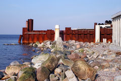 Stenar, vågbrytare och rostig järnvägg på den Östersjön kusten Arkivfoto