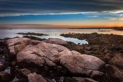 Stenblock på kusten på solnedgången med fyren i avståndet Arkivfoton