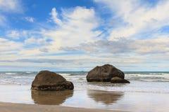 Stenblock reflekterade i de skinande sanderna av en strand royaltyfria bilder
