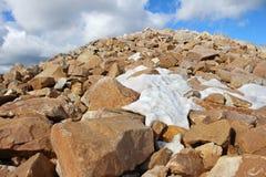 Stenblockfält nära toppmöte av berget med patchy snö Arkivbilder